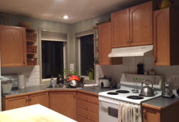 The cupboards above the stove felt orange and ominous. You can see one of the sink bowls filled with pots drying.